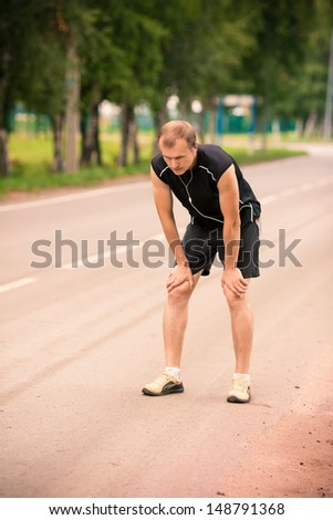 Sportive young man runner having rest after jogging on a road