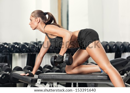 Sportive young woman doing exercise with barbell in the gym - stock photo