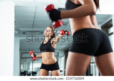Sportive young woman doing exercise with barbell in the gym. - stock photo