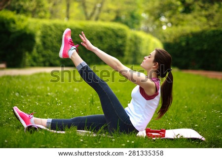 Sportive young woman stretching, doing fitness exercises in green park - stock photo