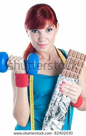Sportive young woman with a dumbbell in one hand and chocolate in another, isolated on white. Sportive life-style - stock photo
