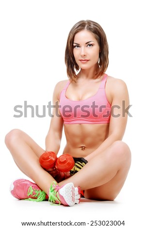 Sportive young woman with beautiful athletic body sitting on a floor with dumbbells. Fitness, bodybuilding. Health care. Isolated over white. - stock photo