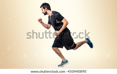 Sportman running fast over ocher background