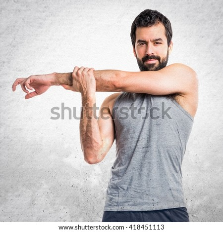 Sportman stretching arms
