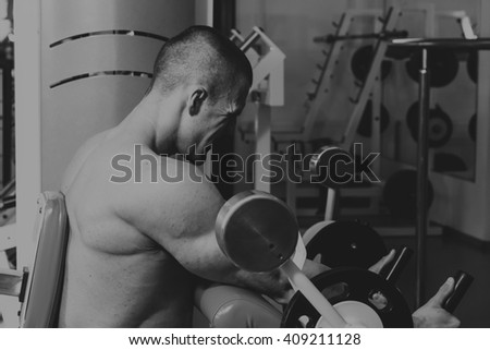 Sports activities in the gym. Strong man doing exercises - stock photo