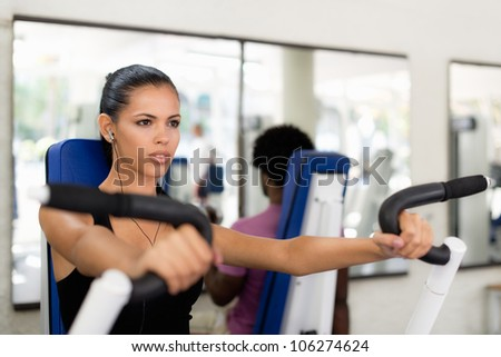 Sports activity, young man and woman exercising and working out in fitness gym - stock photo