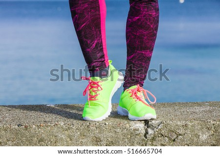 Sports and activities. Part body of training active sporty girl outside. Slim fit legs in vivid color yellow shoes on seaside.