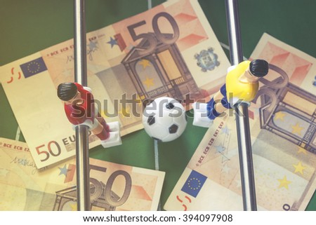 Sports and money. Concept about money spending in football (soccer), sports betting and manipulated fixed matches. Selective focus image cross processed for retro look - stock photo