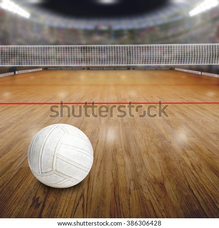 Sports arena full of fans in the stands with volleyball on court. Deliberate focus on ball and shallow depth of field on background net and court. Floodlights flare for effect and copy space. - stock photo