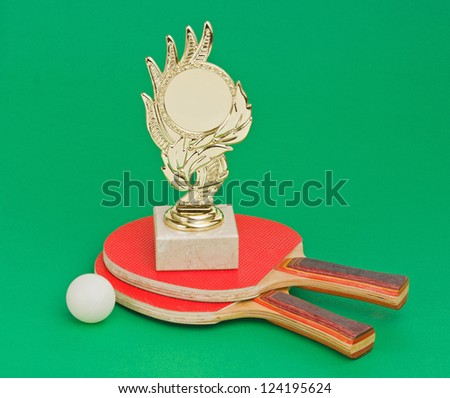 sports awards and  tennis racquets on a green table - stock photo