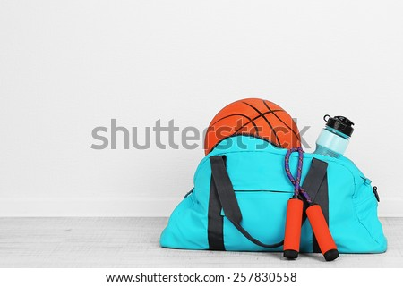 Sports bag with sports equipment in room - stock photo