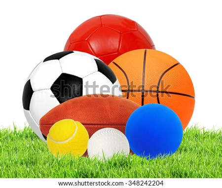 Sports balls on green grass isolated on white background - stock photo