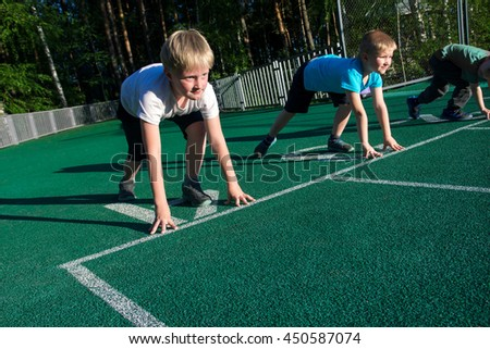 Sports boys (children) on starting position ready to run. Children's sports.