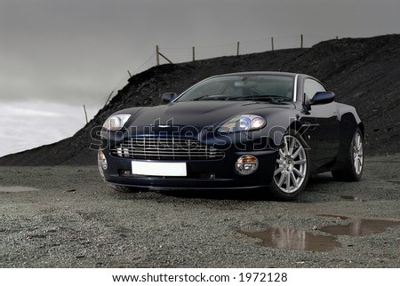 Sports car under storm clouds - stock photo