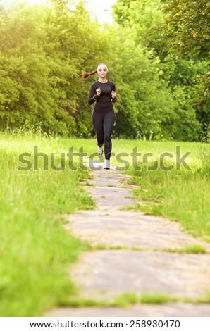 Sports Concept: Positive Sensual Caucasian Sportswoman Running Fast. Vertical Image Composition - stock photo