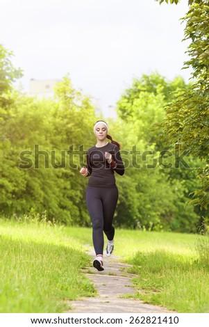 Sports Concept: Positive Sensual Caucasian Sportswoman Running Fast. Vertical Image Compositon - stock photo