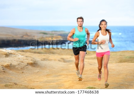 Sports couple jogging for fitness running in beautiful landscape nature outdoors. Young female and male sports athletes training cross-country trail running. Asian woman, Caucasian man,
