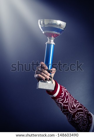 Sports cup in his hand an athlete. - stock photo