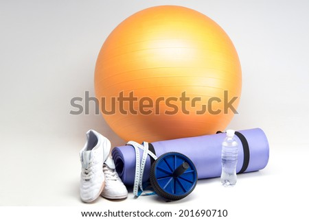 Sports equipment, Fit ball, yoga mat, abs roller, sneakers, measuring tape and water bottle closeup isolated on white - stock photo