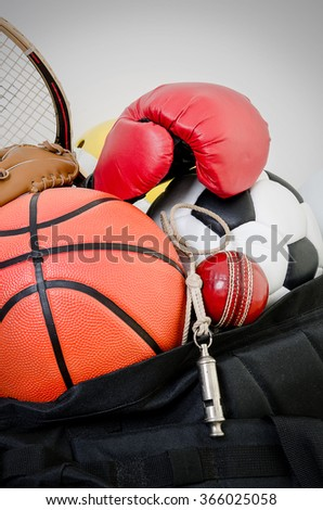 sports equipment in a holdall sports bag on a gym floor. football, baseball, cricket, basketball, boxing, squash and a whistle. - stock photo