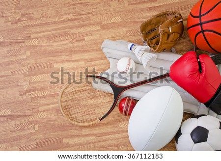 sports equipment on a gym floor, football, rugby, baseball, cricket, basketball, boxing, badminton and squash.