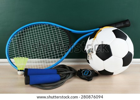 Sports equipment on blackboard background - stock photo