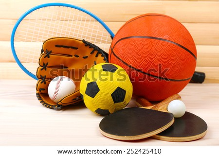 Sports equipment on wooden background - stock photo