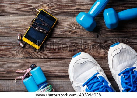 Sports equipment - sneakers, skipping rope, dumbbells, smartphone and headphones. Sport background on wooden floor, top view.