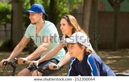 Sports family of three  relaxing in the park with bicycles - stock photo