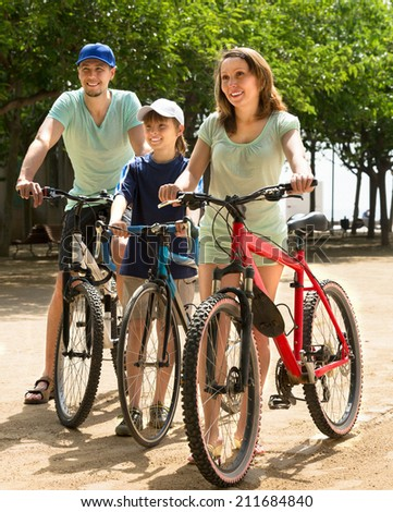 Sports family spending his free time in the park with bicycles - stock photo