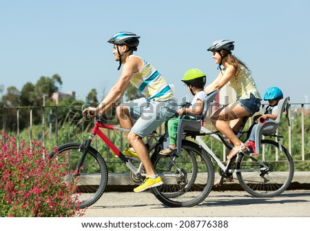 Sports family traveling on bicycles with children in baby bicycle seats - stock photo