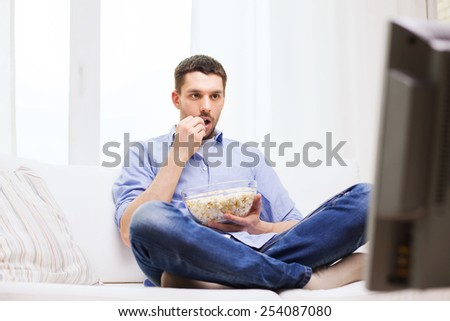 sports, food, happiness and people concept - man watching tv and eating popcorn at home - stock photo