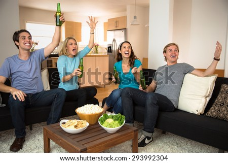 Sports friends fans drinking beer at home celebrating a game on TV - stock photo