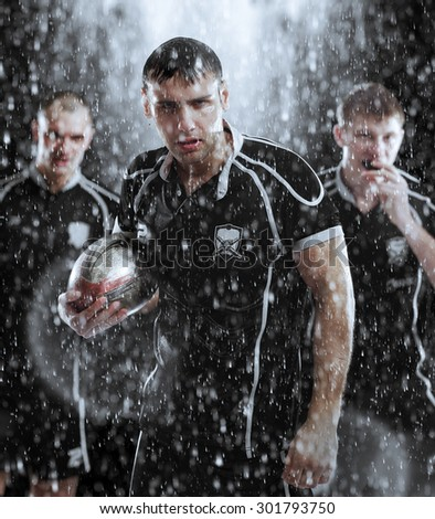 Sports, game, fighting - Rugby players in the rain - stock photo