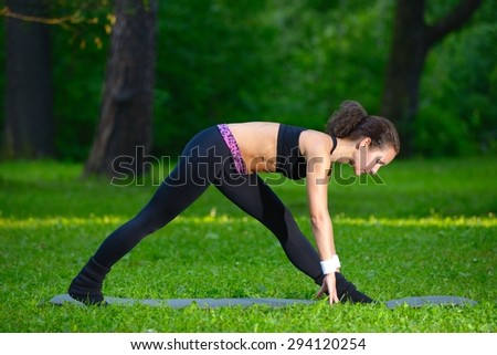 Sports girl does exercises workout outdoors in park