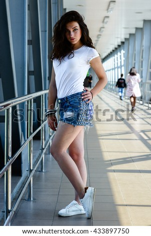 sports girl in a vest and denim shorts