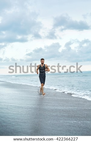 Sports. Handsome Fit Athletic Man Running On Beach. Sporty Runner Jogging Near Sea During Outdoor Workout. Healthy Active Jogger Exercising And Training For Marathon. Fitness Concept