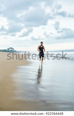 Sports. Handsome Fit Athletic Man Running On Beach. Sporty Runner Jogging Near Sea During Outdoor Workout. Healthy Active Jogger Exercising And Training For Marathon. Fitness Concept - stock photo