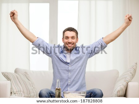 sports, happiness and people concept - smiling man watching sports on tv and supporting team at home - stock photo
