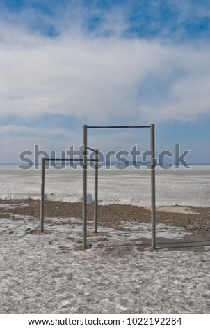 Sports horizontal bars against the blue sky.