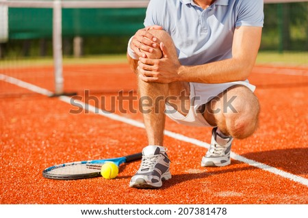 Sports injury. Close-up of tennis player touching his knee while sitting on the tennis court - stock photo