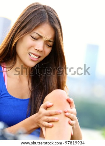 Sports injury. Woman with pain in knee joint sport workout. Young woman fitness model outside. - stock photo