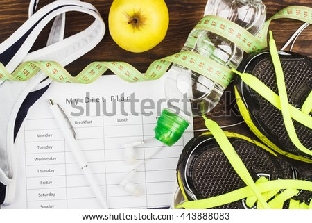 Sports items: sneakers, sport bra, bottle of water and diet plan on the wooden background