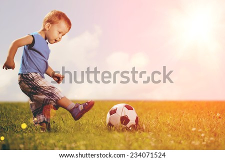 Sports kid. Boy playing football. Baby with ball on sports field. Child plays. - stock photo