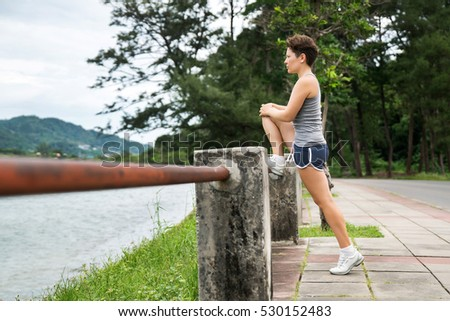 Sports lifestyle. Health and strength. The young girl does a runner stretching before a workout outdoors.