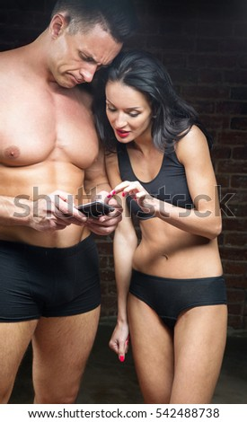 Sports man and woman in sports lingerie looking in the phone in studio