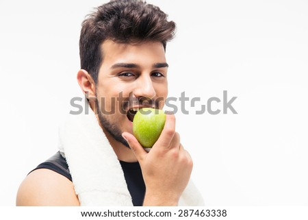 Sports man eating apple and looking at camera isolated on a white background