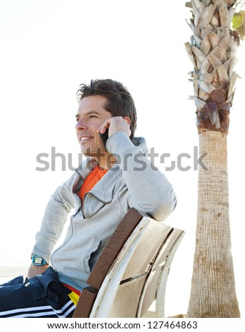 "Sports man smiling and making a call on his ""smart phone"" while taking a break from exercising on a sunny day by the sea."