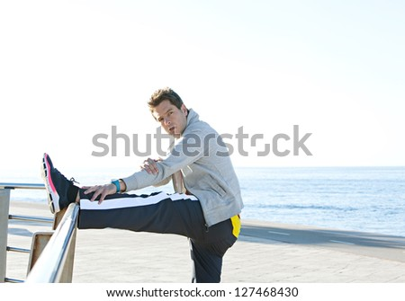Sports man stretching his legs while exercising by the sea side, with a blue sky and ocean in the background, outdoors. - stock photo