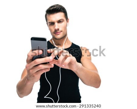 Sports man using smartphone with headphones isolated on a white background. Focus on smartphone - stock photo